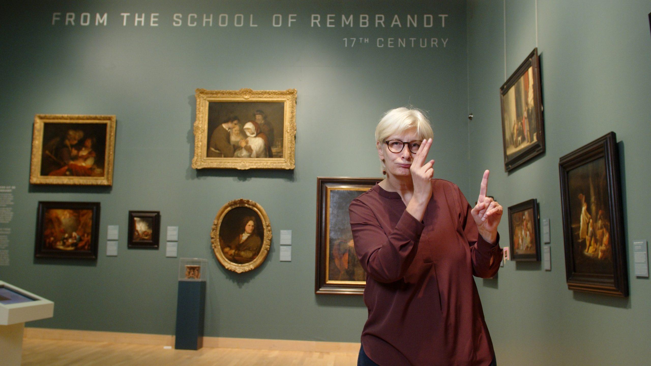 Foto ID: Lara Cox, Een Dove Vrouw Met Blond Haar En Een Donkerrode Shirt Staat In Het Dordrechts Museum Te Vertellen Over De Kunst Die Er Hangt.
